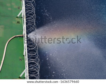 rain bow on water spray from fire hose on a cargo ship which fitted with razor wire during passing piracy high risk area.  Сток-фото ©