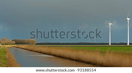 Rain clouds over water and agriculture - stock photo