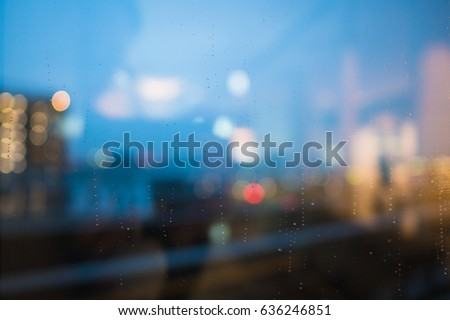 rain drop on clear glass window, reflection of blurred airport terminal and light bokeh from outside, beautiful color abstract for background