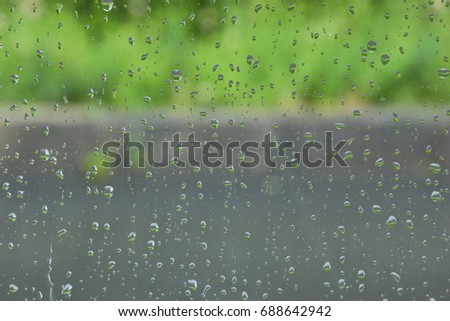 Rain drop on the glass windows. Condensation on the glass in the morning. raining on the glass off window ferry boats for background. on window and a cloudy stormy sky outside, . Natural Pattern  #688642942