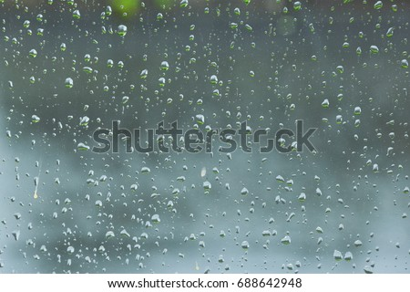 Rain drop on the glass windows. Condensation on the glass in the morning. raining on the glass off window ferry boats for background. on window and a cloudy stormy sky outside, . Natural Pattern  #688642948