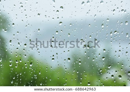 Rain drop on the glass windows. Condensation on the glass in the morning. raining on the glass off window ferry boats for background. on window and a cloudy stormy sky outside, . Natural Pattern  #688642963
