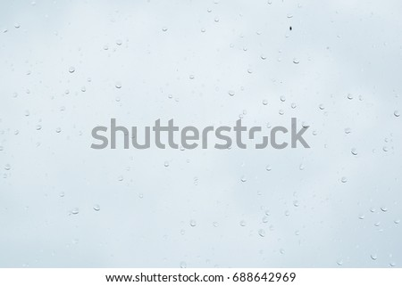 Rain drop on the glass windows. Condensation on the glass in the morning. raining on the glass off window ferry boats for background. on window and a cloudy stormy sky outside, . Natural Pattern  #688642969