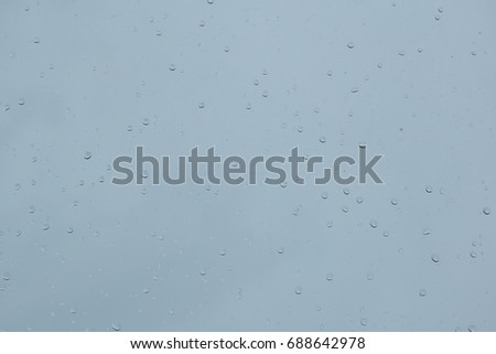 Rain drop on the glass windows. Condensation on the glass in the morning. raining on the glass off window ferry boats for background. on window and a cloudy stormy sky outside, . Natural Pattern  #688642978