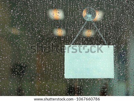 Rain drop with blank sign board hanging on glass door.