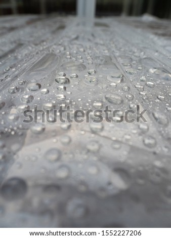 Rain droplets isolated on a light surface. Wet surface background. #1552227206