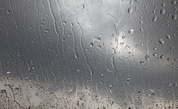 Rain droplets on a window glass pane with dark stormy clouds in the background.