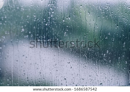 rain drops during raining in rainy day outside window glass with blurred background with water droplet flow down the surface Foto stock ©