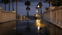 Rain drops, evening dark sky with clouds, Oceanside California USA. Empty pier, puddle, palms in twilight dusk. Reflection of lantern lights, illuminated wet broadwalk. Pacific ocean beach at night.