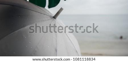 Rain drops falling from a white umbrella concept for bad weather. Umbrella in the rain. Rain umbrella with rain drops #1081118834