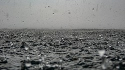 Rain drops into the endless ocean, close up. It briefly bounces back to the air after it hits the sea surface.