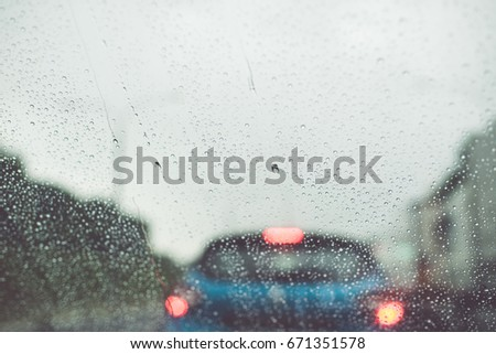 Rain drops on a car window/toned photo #671351578