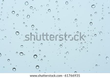 Rain drops on a window against cloudy sky.