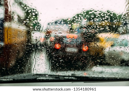 Rain drops on car glass with blur traffic jam on the road in background at Kolkata, India. #1354180961