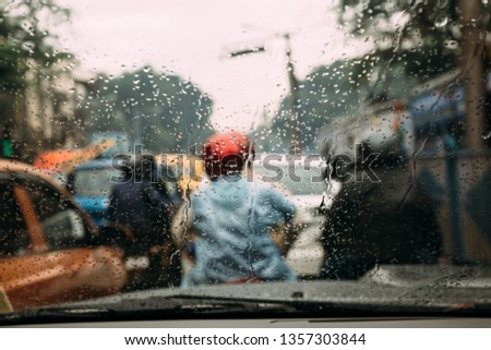 Rain drops on car glass with blur traffic jam on the road in background at Kolkata, India. #1357303844