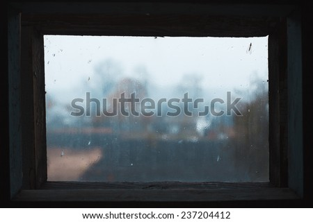 Rain drops on glass in frame. Texture of glass. Rainy weather. Sad autumn mood. Rural landscape outside window