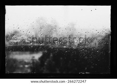 Rain drops on glass in frame. Texture of glass. Rainy weather. Sad autumn mood. Rural landscape outside window. Black and white photo
