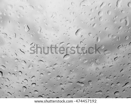 Rain drops on glass window grey sky background #474457192