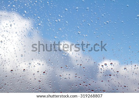 rain drops on glass with blue sky white clouds #319268807