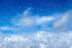 Rain drops on the glass. Beautiful blue and white sky. Sky background