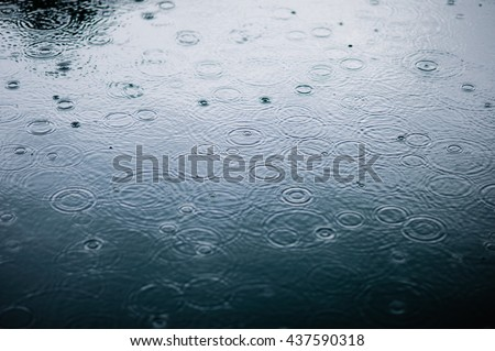 rain drops on the surface of water in a puddle with graduated shade of black shadow and reflection of blue sky