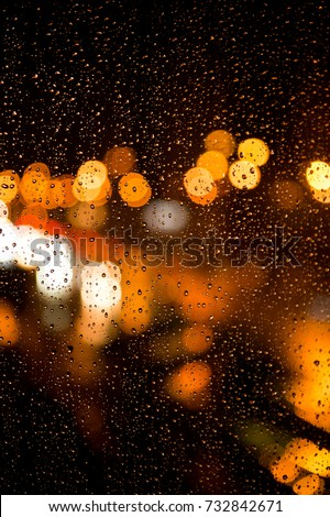 Stock Photo Rain drops on the window. Rain drops on the glass on a background of a night blurred city. Rainy weather. Outside the window is a blurred city. Bokeh night city.