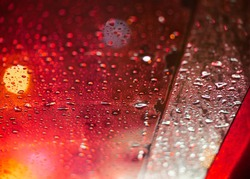 rain drops on transparent glass window , view to traffic outside with bokeh and red light on the road , and seeing water splashing line on the right by wipers