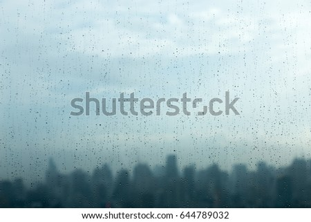 Rain drops on window glass and blurred cityscape and sunlight in background. #644789032