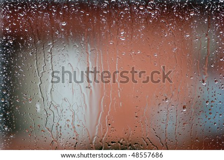 Rain drops on window glass. Weather outside, poor conditions drab dreary bleak cold, water streaming down inside of fogged glass.