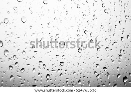 Rain drops on window glasses surface with cloudy background . Natural Pattern of raindrops black and white on cloudy background. #624765536