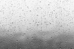 Rain drops on window glasses surface with cloudy background . Natural Pattern of raindrops isolated on cloudy background.