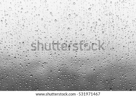 Photo of  Rain drops on window glasses surface with cloudy background . Natural Pattern of raindrops isolated on cloudy background.