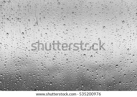 Rain drops on window glasses surface with cloudy background . Natural Pattern of raindrops isolated on cloudy background. #535200976