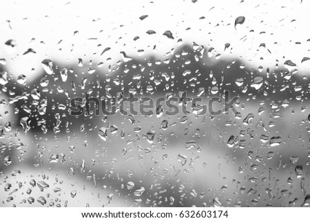 Rain drops on window glasses surface with cloudy background . Natural Pattern of raindrops on sky cloudy black and white background. Defocused #632603174