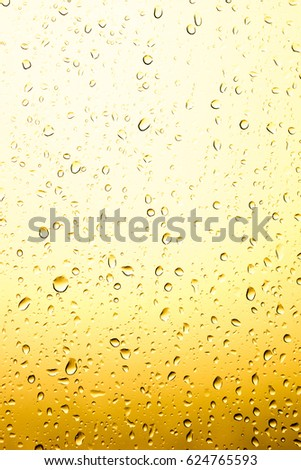 Rain drops on window glasses surface with cloudy background . Natural Pattern of raindrops yellow and white on cloudy background. #624765593