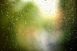 Rain drops on window on autumn day. Yellow and green tree on background.