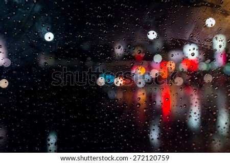 Stock Photo Rain drops on window with street bokeh lights
