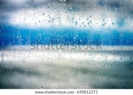 Rain drops on windowpane with sunbeams shine through the clouds and reflected in the sea #690812371