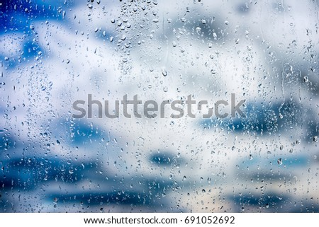 Rain drops on windowpane with sunbeams shine through the clouds and reflected in the sea #691052692