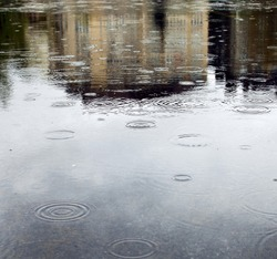 Rain drops rippling in a puddle with buildings, sky and trees reflection.