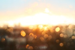 Rain drops texture on window glass with gorgeous vintage orange amber sunset light abstract blurred cityscape skyline bokeh background. Soft focus