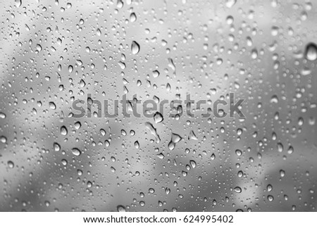 Rain drops, water drops of rain on a window glass black and white background, abstract defocused with space #624995402