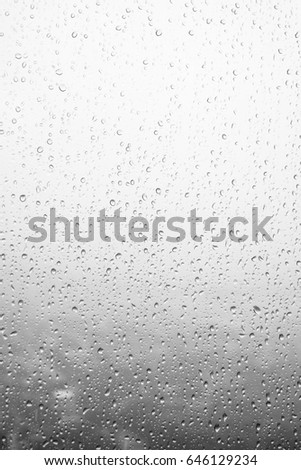 Rain drops, water drops of rain on a window glass. blurred lights city with sky clouds in rainy day, abstract blue background texture, view beautiful from outside window #646129234
