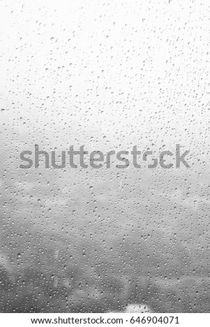 Rain drops, water drops of rain on a window glass. blurred lights city with sky clouds in rainy day, abstract blue background texture, view beautiful from outside window #646904071