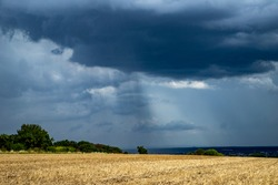 rain falls in streaks from a cloud in countryside area, field in the foreground, weather