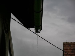 Rain flowing through the missing gutter on a rainy summer day at a residential house.