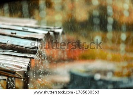 Rain flows down from a tin roof ストックフォト ©