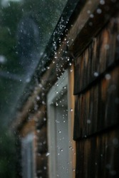 Rain hitting hard, splashing off a roof. High speed photography freezing droplets in mid air.