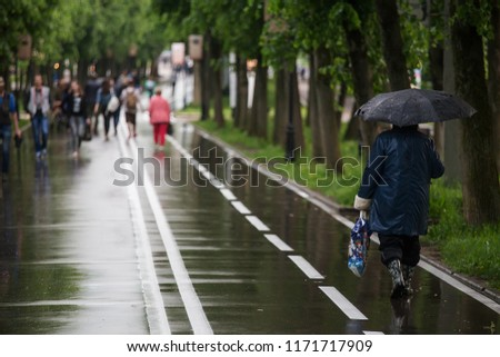 rain in the city, wet clothes, people go under umbrellas, fleeing from bad weather and water pouring from the sky, autumn weather, wet asphalt and city streets during a downpour