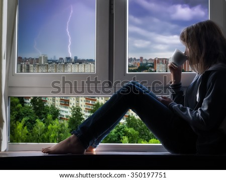 Rain, lightning outside. The girl is sitting on the window, looking at the city and drinking coffee or tea. Outside the window of the building. Thunderstorm over the city, a flash of lightning.